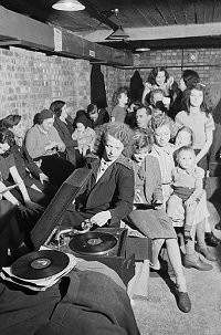 396px-A_young_woman_plays_a_gramophone_in_an_air_raid_shelter_in_north_London_during_1940__D1631
